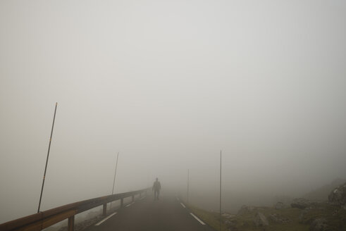 Mid distance of man walking on mountain road against sky in foggy weather - MASF04912