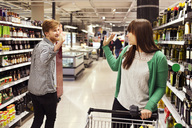 Man and woman waving at each other in supermarket - MASF04915