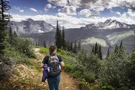 Rear view of woman looking away walking on mountain - CAVF42129