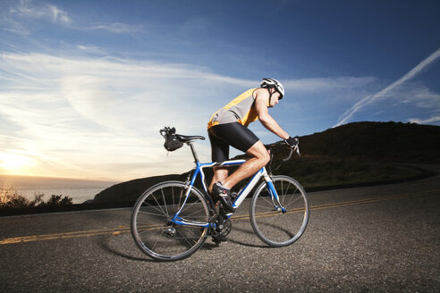 Side view of cyclist riding bicycle on road against sky - CAVF42162