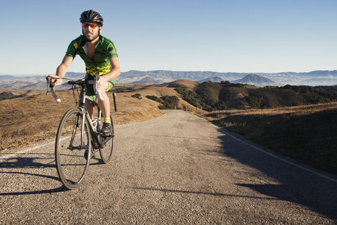 Man riding bicycle on gravel road against clear sky - CAVF42183