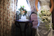 Midsection of bride holding rose bouquet standing at home during wedding day - CAVF42270
