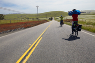 Friends enjoying while cycling on country road amidst field against sky - CAVF42300