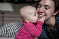 Playful daughter biting mother on bed at home - CAVF42327