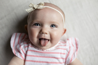Close-up portrait of happy baby girl sticking out tongue while relaxing on bed at home - CAVF42354