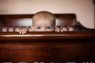 Portrait of baby girl peeking over crib - CAVF42384