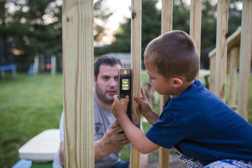 Father teaching son to use spirit level on wooden frame at yard - CAVF42387