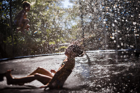 Playful siblings playing on wet trampoline at playground - CAVF42393