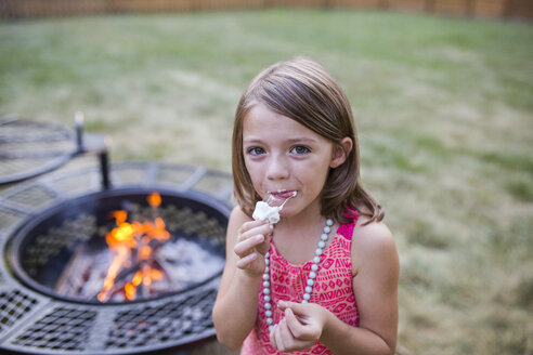 High angle portrait of girl eating roasted marshmallow while standing at yard with fire pit in background - CAVF42456