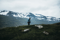 Man standing on cliff against snowcapped mountains - CAVF42474
