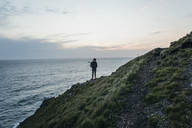 Hiker standing on mountain by sea against sky during sunset - CAVF42483