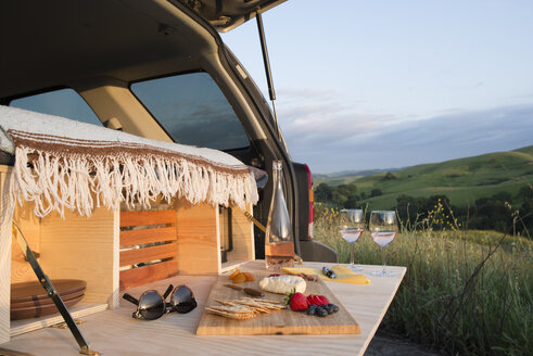 Food on cutting board at car trunk of sports utility vehicle by rolling landscape - CAVF42495