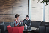 Cheerful business couple enjoying drinks while sitting in restaurant - CAVF42657