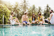 Cheerful friends spending leisure time at poolside - CAVF42708