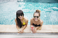 High angle portrait of happy friends holding drinks while relaxing in swimming pool - CAVF42723