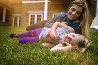 Mother looking at thoughtful girl lying on grassy field in yard - CAVF42831
