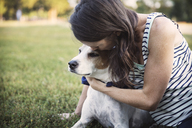 Loving woman kissing dog while resting on grassy field at park - CAVF42867