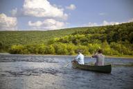 Friends traveling in canoe against sky - CAVF42894
