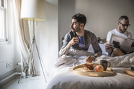 Gay man having breakfast while partner reading newspaper on bed at home - CAVF43005