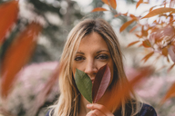 Portrait of young woman with two leaves - AFVF00436