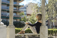 Young woman relaxing on bench - AFVF00445
