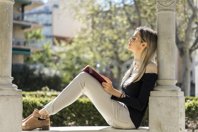 Young woman with notebook relaxing on bench - AFVF00448