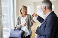 Happy male real estate agent giving keys to woman in new house - MASF04928