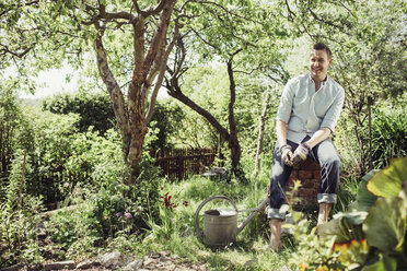 Happy young man relaxing while gardening at yard - MASF04931