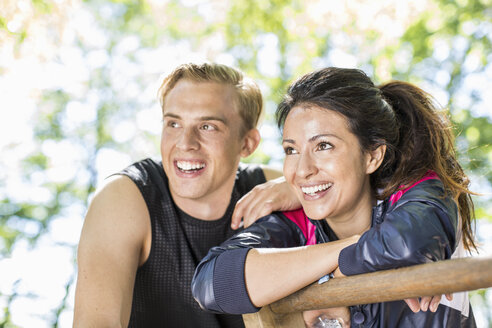 Happy multi-ethnic couple looking away at outdoor gym - MASF04934