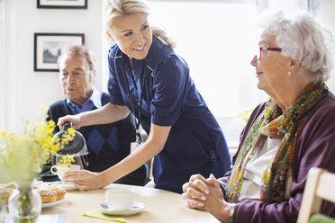 Happy female caretaker serving coffee to senior people at nursing home - MASF04943