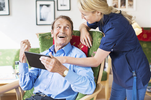 Happy senior man and female caretaker using digital tablet at nursing home - MASF04949