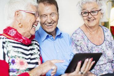 Happy senior friends using digital tablet at nursing home - MASF04952