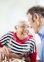 Happy senior couple looking at each other while playing chess in nursing home - MASF04955