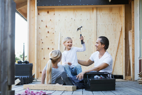 Happy parents with daughter holding hammer while sitting outside house - MASF04973