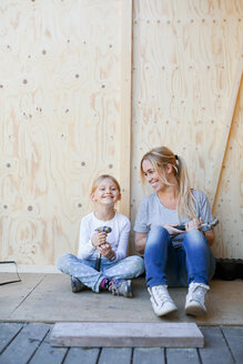 Happy mother and daughter holding hammers against wall of house being renovated - MASF04976