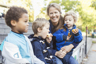 Happy teacher sitting with children outside kindergarten - MASF04982