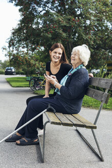 Happy grandmother and granddaughter using mobile phone on park bench - MASF04988