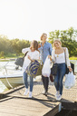 Happy friends with luggage walking on pier by lake against clear sky - MASF04991