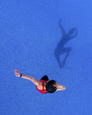 Jumping young woman and her shadow on blue background, top view - STSF01492