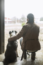 Full length rear view of young woman arm around dog in doorway of horse stable - MASF04995