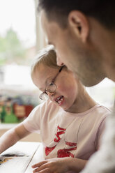 Girl with down syndrome studying by father at home - MASF05001