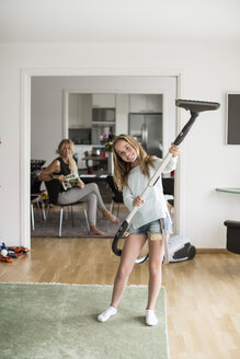 Full length portrait of playful girl holding vacuum cleaner at home with mother sitting in background - MASF05010