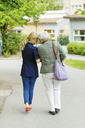 Full length rear view of affectionate female caretaker and senior woman walking on street - MASF05013