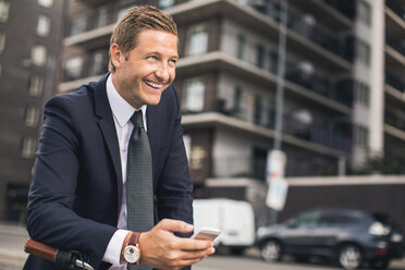 Happy businessman using smart phone in city - MASF05019