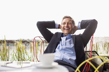 Happy businessman relaxing at outdoor cafe against clear sky - MASF05022