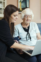 Grandmother and granddaughter using laptop at home - MASF05028