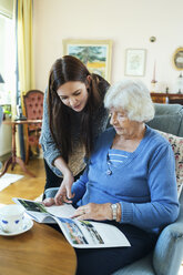 Grandmother and granddaughter reading magazine together in living room - MASF05031