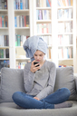 Girl wearing towel turban sitting on couch at home looking at cell phone - LVF06882