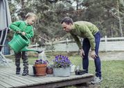 Father and son gardening together in yard - MASF05047