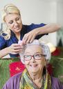 Female caretaker putting curlers to senior woman's hair at nursing home - MASF05065